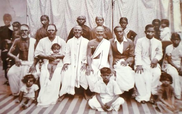 My mother's paternal grandfather, my great-grandfather, N. Kuppuswamy, is seated in the centre. He is wearing an angavastram or upper garment. His wife and my great grandmother, Alamelu is standing behind him.