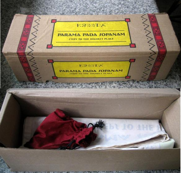 "Top: The ""boxed"" game. Bottom: The box opens to reveal a little cloth pouch containing little wooden counters, two elongated metal dies, and an information booklet (not in picture)"