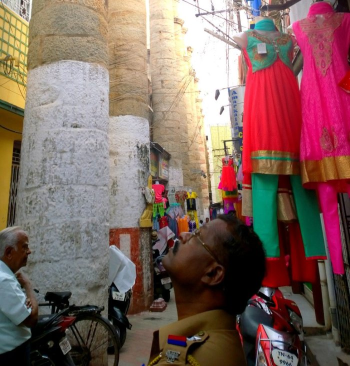 A policeman looks up in awe at the Pathu Thoongal or 10 pillars, which are the only things remaining from the Ranga Vilas, a palace built by Thirumalai Nayak